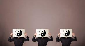 Knappe mensen in het formele gesturing met yin yang teken op cardbo Royalty-vrije Stock Afbeeldingen