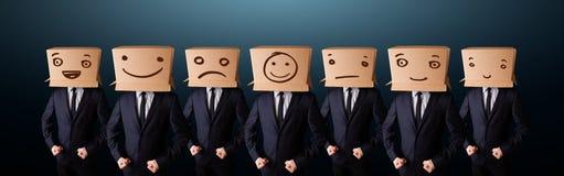Knappe mensen in kostuum het gesturing met getrokken smileygezichten op doos royalty-vrije stock afbeelding