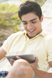 Knappe mensenlezing op een tablet Royalty-vrije Stock Afbeelding