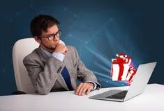 Knappe mensenzitting bij bureau en het typen op laptop met huidige B royalty-vrije stock foto's