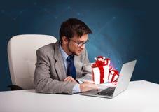 Knappe mensenzitting bij bureau en het typen op laptop met huidige B stock afbeeldingen