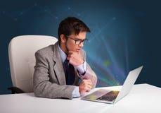 Knappe mensenzitting bij bureau en het typen op laptop met samenvatting stock afbeeldingen