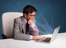 Knappe mensenzitting bij bureau en het typen op laptop met samenvatting stock afbeelding