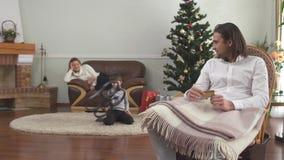 Knappe mensenzitting in de creditcard van de leunstoelholding Moeder en weinig zoon op de achtergrond De gelukkige familie viert stock video