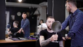 Knappe mensenzitting op stoel in herenkapper en het bekijken zich in grote spiegel achter het houden van het kleine kijken binnen stock videobeelden