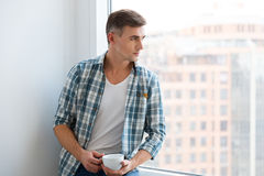 Knappe mensenzitting op vensterbank en het drinken koffie Royalty-vrije Stock Fotografie