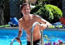 Knappe midden oude mens die uit zwembad beklimt stock afbeeldingen