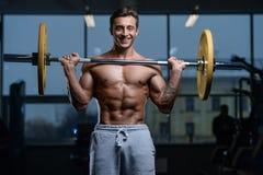 Knappe model jonge mensentraining in gymnastiek Stock Foto's