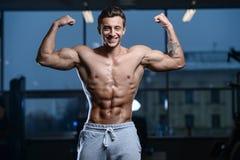 Knappe model jonge mensentraining in gymnastiek Stock Afbeeldingen