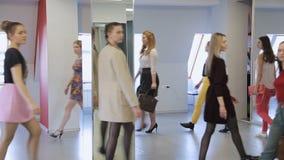 Knappe modellen in modieuze kleren die in loopbrug in balzaal opleiden stock footage