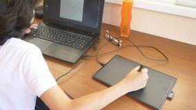 Knappe moderne jongenstiener die aan een grafische tablet werken Hij bekijkt het laptop scherm 4k, langzame motie stock footage