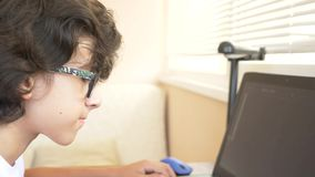 Knappe moderne jongenstiener die aan een grafische tablet werken Hij bekijkt het laptop scherm 4k, langzame motie stock videobeelden