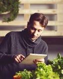 Knappe moderne kweker die zijn tablet gebruiken terwijl het groeien Ind. plant royalty-vrije stock fotografie