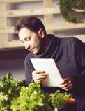 Knappe moderne kweker die zijn tablet gebruiken terwijl het groeien Ind. plant royalty-vrije stock afbeelding