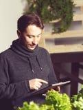 Knappe moderne kweker die zijn tablet gebruiken terwijl het groeien Ind. plant stock foto's