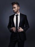 Knappe modieuze mens in zwart kostuum Stock Afbeelding