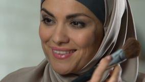 Knappe moslimvrouw die gezichtspoeder toepassen, die samenstelling, luxeschoonheidsmiddelen doen stock videobeelden