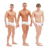 Knappe naakte kerels die in witte memoranda stellen Stock Afbeelding