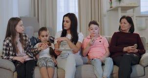 Knappe oma met haar dochter en kleinkinderen die klaar voor een familiefilm nemen zij wat snacks het zitten worden stock video