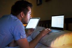 Knappe ondernemersmens die Internet in bed doorbladeren bij nacht Stock Foto