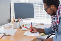 Knappe ontwerpertekening iets met een rood potlood stock afbeelding