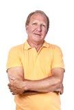 Knappe oude mens met oranje polo-overhemd gekruiste handen Stock Afbeelding