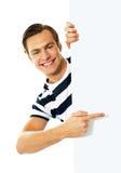 Knappe persoon die naar leeg uithangbord richt Stock Foto