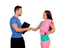 Knappe persoonlijke trainer met een aantrekkelijk meisje stock afbeelding