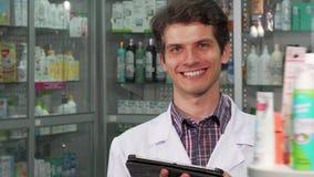 Knappe professionele apotheker die inventaris doen die digitale tablet gebruiken stock foto