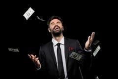 Knappe rijke opgewekte zakenman die dollarbankbiljetten werpen, Stock Foto's