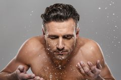 Knappe rijpe mens die zijn gezicht wassen stock fotografie