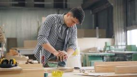 Knappe schrijnwerker die oppoetsende machine met behulp van om hout in workshop op te poetsen stock footage