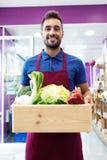Knappe sellman holding een doos met vruchten en groenten in fruitshop Royalty-vrije Stock Foto