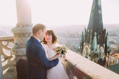 Knappe sensuele bruidegom die jonggehuwdebruid koesteren van erachter bij oud kasteelbalkon met stadsachtergrond royalty-vrije stock foto's