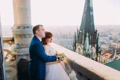 Knappe sensuele bruidegom die jonggehuwdebruid koesteren van erachter bij oud kasteelbalkon met stadsachtergrond stock fotografie