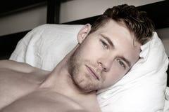 Knappe, sexy knappe mens met groen ogen eerst ding in de ochtend, die camera in een bed met witte bladen bekijken royalty-vrije stock afbeeldingen
