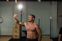Knappe shirtless spierbodybuildermens die selfie met celtelefoon nemen stock foto