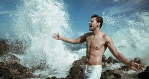 Knappe, spiermens met ruwe oceaan op de achtergrond Royalty-vrije Stock Afbeeldingen