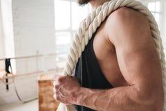 Knappe spiermensenholding op de training van de schouderkabel in lichte gymnastiek stock afbeelding