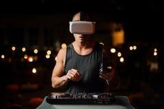 Knappe spiernachtclub DJ in de glazen van de nachtvisie stock foto