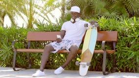 Knappe sportieve Afrikaanse mens met een skateboard stock footage
