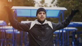 Knappe sportieve jonge mens die opwarmingsoefening doen alvorens bij de winterpark op te leiden Royalty-vrije Stock Foto's