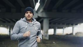 Knappe sportieve mensenagent op oortelefoons zetten en begin die bij stedelijke in openlucht stadsplaats lopen in de winter Stock Fotografie