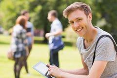 Knappe student die buiten op campus bestuderen Stock Fotografie