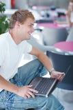 Knappe student die een computer met behulp van Stock Afbeeldingen