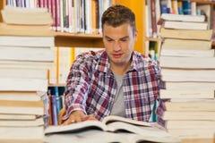 Knappe student die tussen stapels van boeken bestuderen royalty-vrije stock fotografie