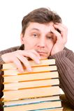 Knappe studentenzitting tussen studieboeken Stock Fotografie