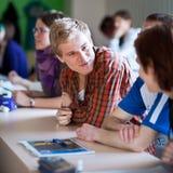 Knappe studentzitting in een klaslokaal stock foto