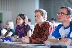 Knappe studentzitting in een klaslokaalhoogtepunt van studenten stock afbeelding