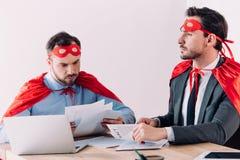 knappe super zakenlieden in maskers en kaap die met documenten werken royalty-vrije stock fotografie